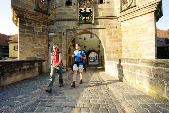 Zwei Wanderer vor Torbogen